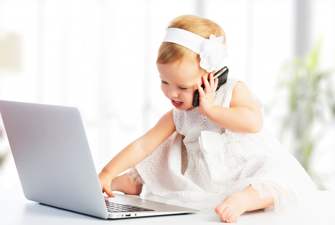 Image of baby on the phone in front of a computer